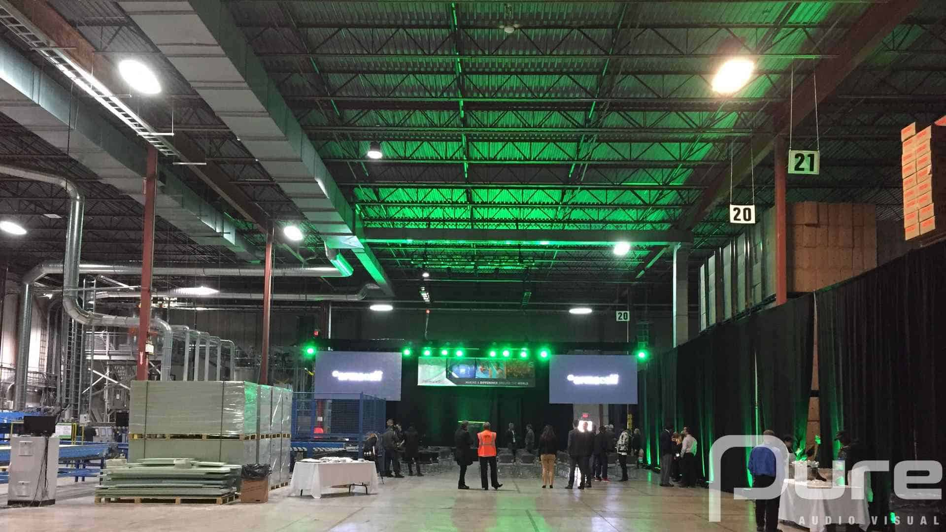 A presentation with a small stage, podium, 2 LED video walls, truss, and auras in a warehouse space