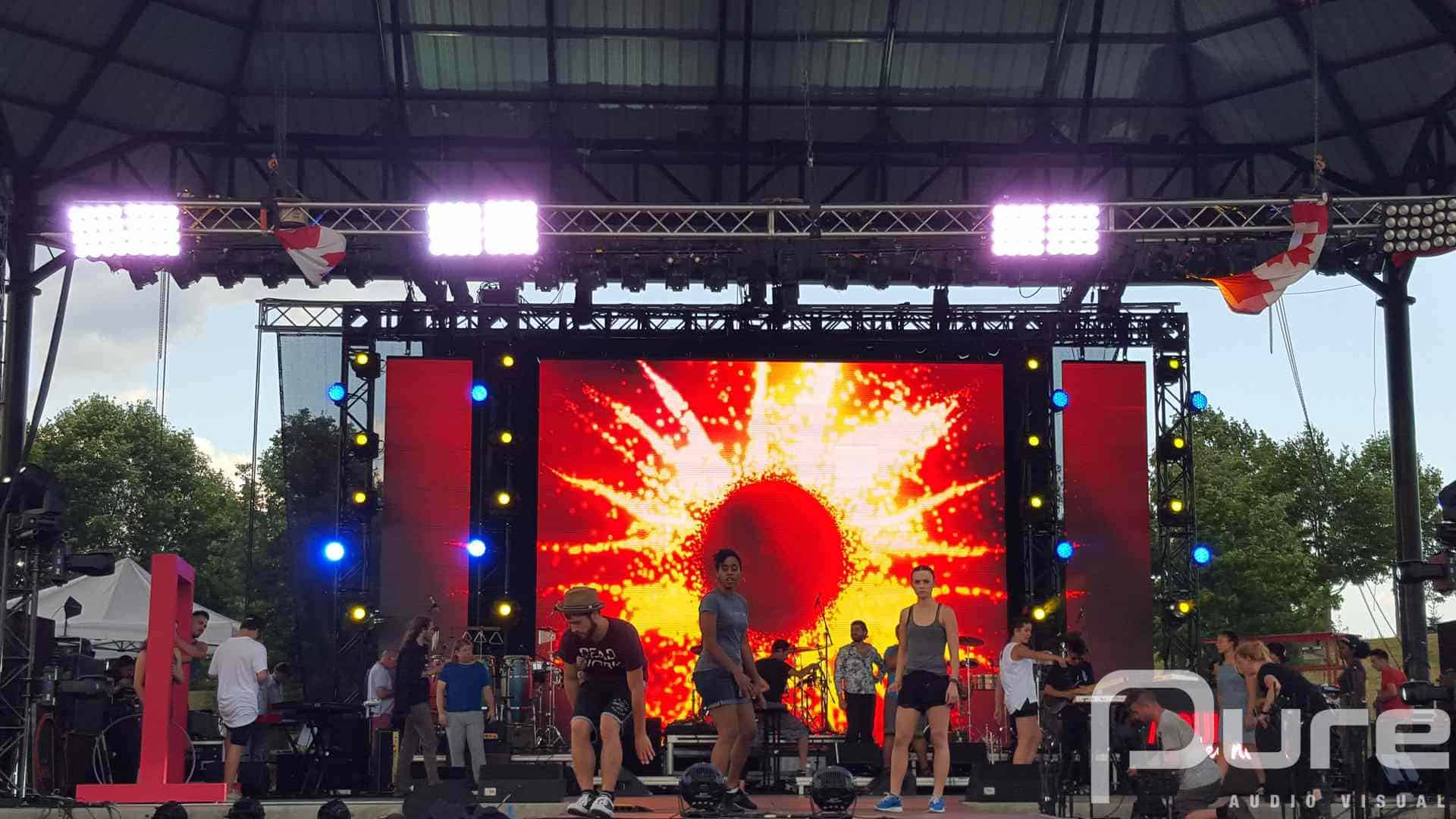 Outdoor performance on stage with LED video wall, truss, and moving heads
