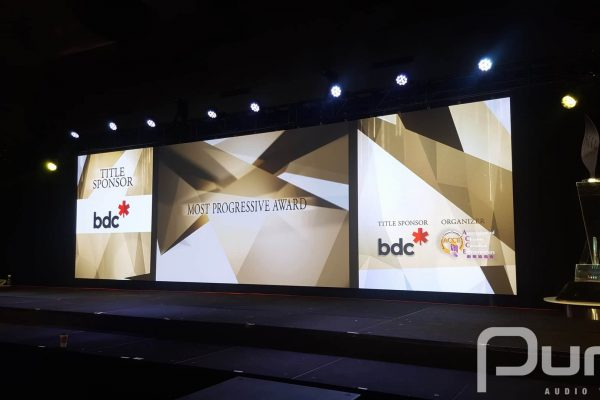 An LED video wall, truss, LED parcans, and podium at an awards gala