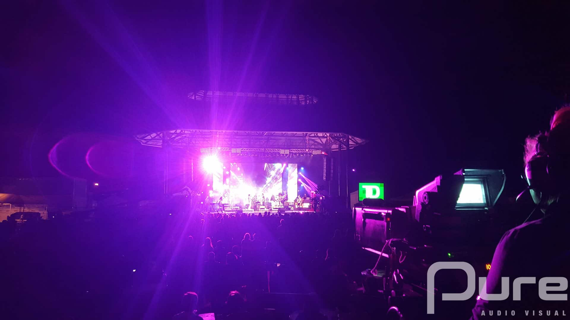 An outdoor concert with an LED video wall, line array, and moving heads
